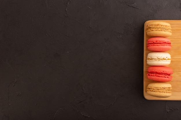 Una vista dall'alto ha colorato i macarons francesi deliziosi sullo scrittorio di legno e sulla caramella di zucchero del biscotto della torta della tavola scura dolce Foto Gratuite