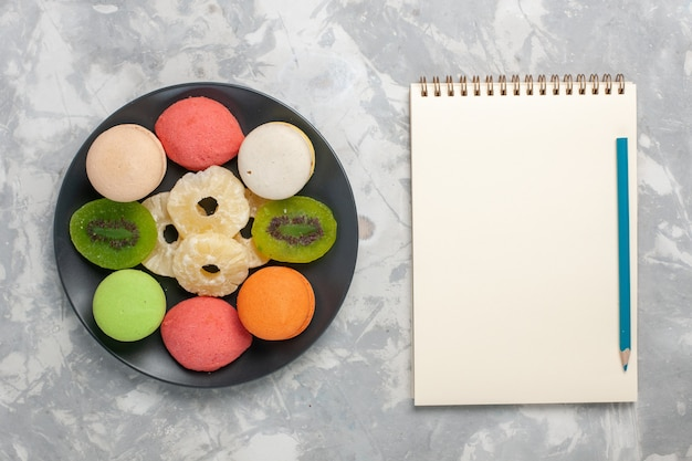 Top view colored little cakes with dried pineapple rings on light-white desk Free Photo