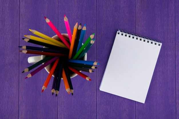 Top view of colored pencils in cup and note pad on purple background Free Photo