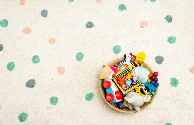 Top view on colorful baby toys on a carpet  toys in the floor with copyspace Premium Photo