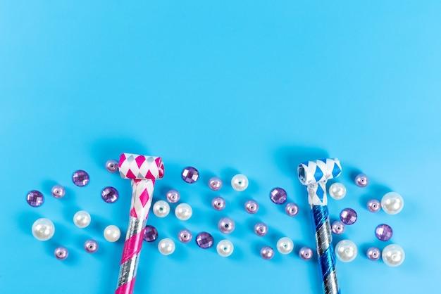 Un compleanno colorato con vista dall'alto fischia insieme a palline di gioielli isolate sull'azzurro Foto Gratuite