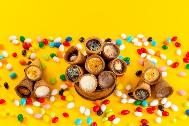 Una vista dall'alto caramelle colorate insieme a gelato di corno su giallo Foto Gratuite