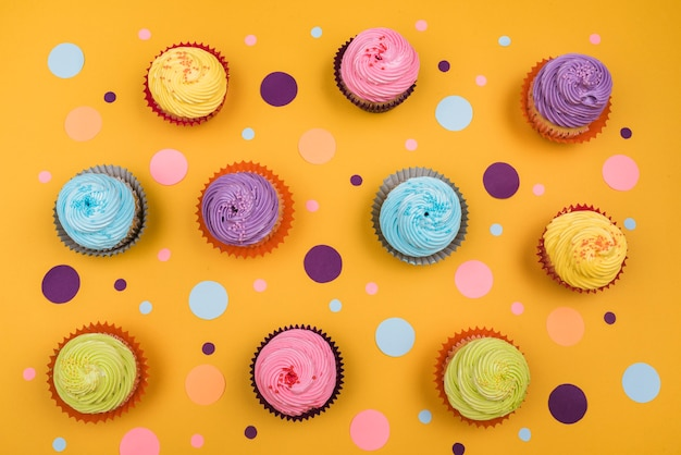 Top view colorful cupcakes on table Free Photo