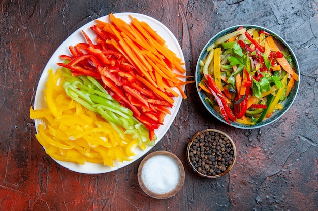 Vista dall'alto peperoni colorati tagliati su insalata di verdure piatto bianco nella ciotola pepe nero sale aglio sul tavolo rosso scuro Foto Gratuite