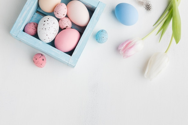 Top view of colorful eggs for easter with tulips Free Photo