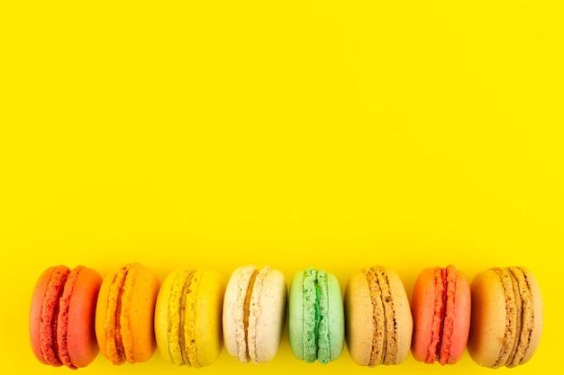 Una vista dall'alto macarons francesi colorati yummy sul dolce giallo del biscotto della torta dello zucchero dello scrittorio Foto Gratuite