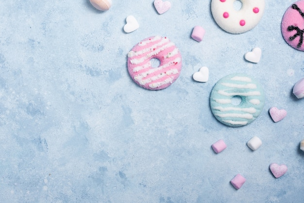 Top view of colorful glazed doughnuts with marshmallow and candy Free Photo