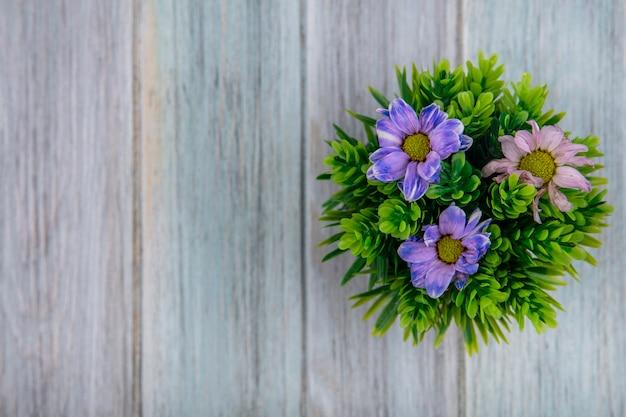 Vista dall'alto di fiori colorati adorabili della margherita su un fondo di legno grigio con lo spazio della copia Foto Gratuite