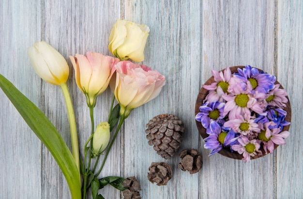 Vista dall'alto di fiori colorati adorabili della margherita su una ciotola di legno con pigne e tulipano bianco su un fondo di legno grigio Foto Gratuite