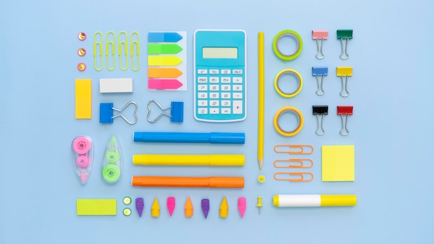 Top view of colorful office stationery with calculator and paper clips Free Photo