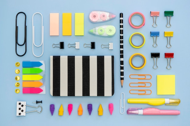 Top view of colorful office stationery with paper clips and tape Free Photo
