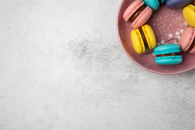 Top view of colorful pastel macarons on white background. Free Photo