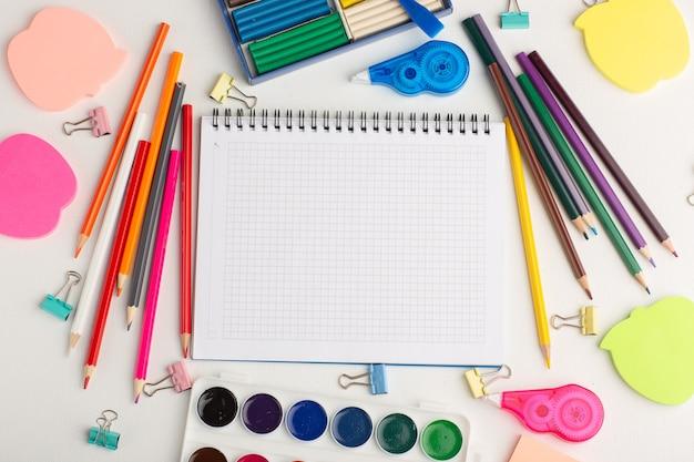 ペンキのメモ帳と白い机の上のステッカーとカラーペイントを描く上面図カラフルな鉛筆 無料写真