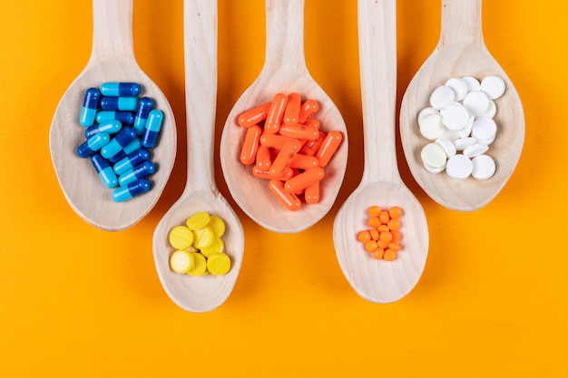 Top view of colorful pills in wooden spoons on orange background. horizontal Free Photo