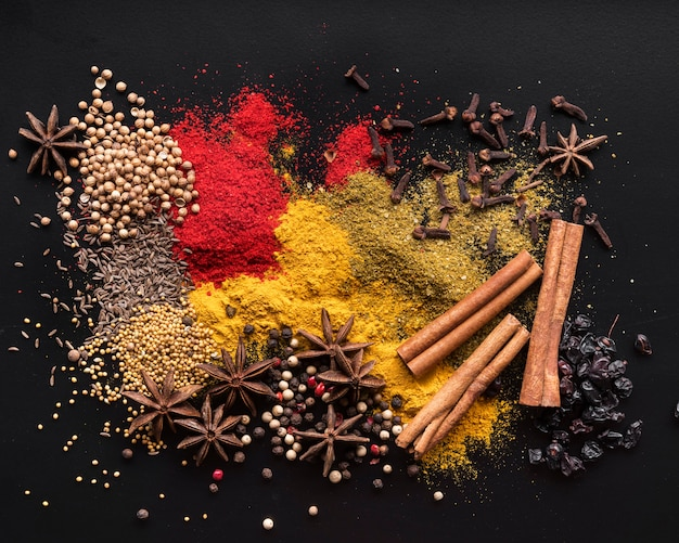 Top view colorful spices on black background Premium Photo