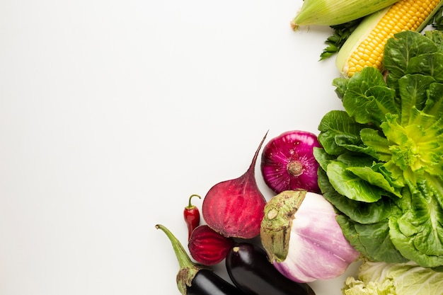 Top view colorful veggies on white background with copy space Free Photo