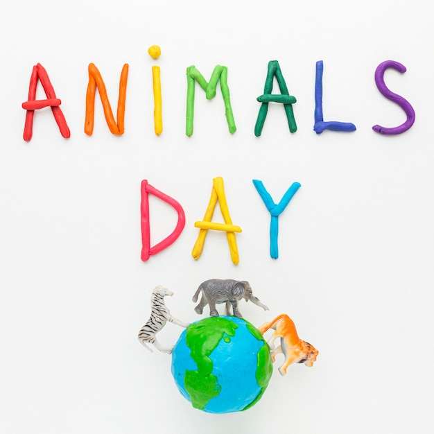 Top view of colorful writing and planet earth with animal figurines for animal day Free Photo