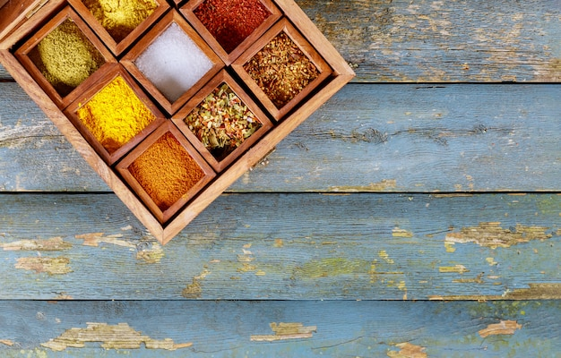 Top view of colourful spices seasonings in wooden box. Premium Photo