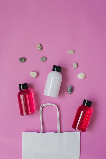 Top view composition of small travel bottles for cosmetics, shower gel, shampoo and hair balm and sea pebbles. Premium Photo