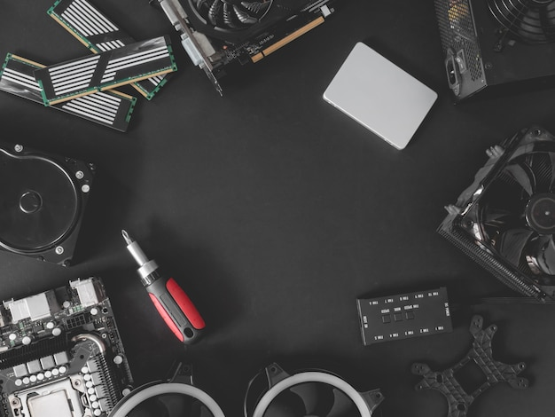 Top view of computer parts with harddisk, ram, cpu, graphics card, and motherboard on black table background. Premium Photo