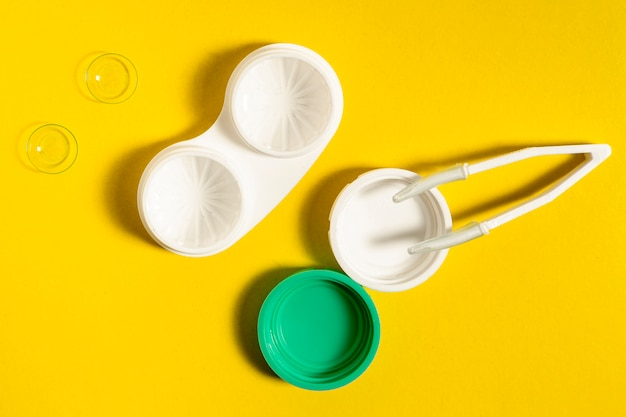 Top view of contact lenses case and tweezers Free Photo