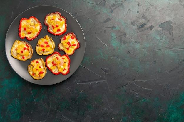暗い表面のプレートの内側の昼食のための上面図調理されたピーマン 無料写真