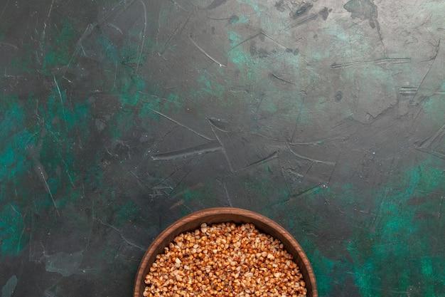 Vista dall'alto pasto gustoso di grano saraceno cucinato all'interno del piatto marrone sulla superficie verde scuro Foto Gratuite