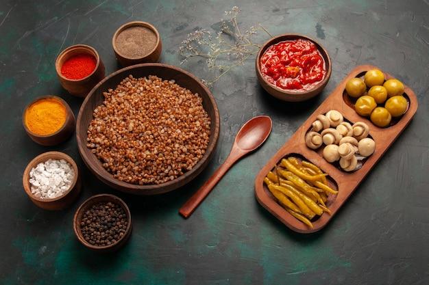 Вид сверху приготовленной гречки с томатным соусом и разными приправами на зеленой поверхности Бесплатные Фотографии