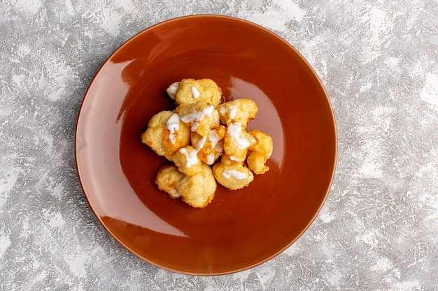 Top view of cooked cauliflower inside brown plate on light surface Free Photo