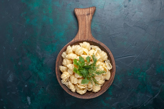 Вид сверху приготовленные макароны из теста с зеленью внутри тарелки на темной поверхности Бесплатные Фотографии