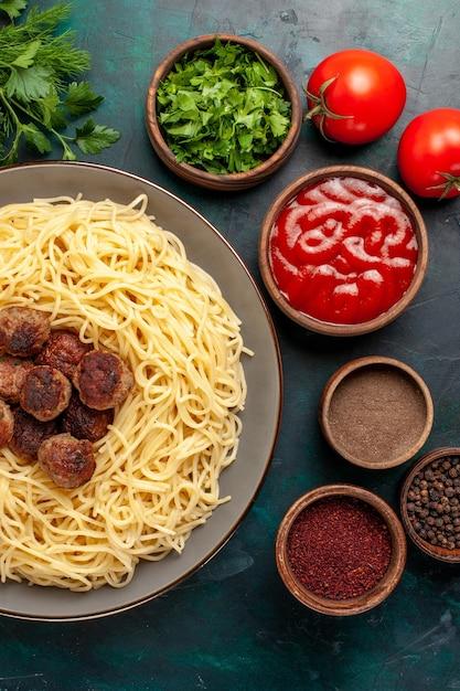 紺色の机の上にさまざまな調味料で調理されたイタリアンパスタの上面図 無料写真