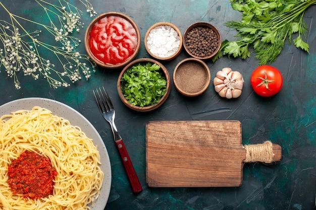 상위 뷰는 파란색 표면에 고기와 다른 조미료와 함께 이탈리아 파스타 요리 무료 사진