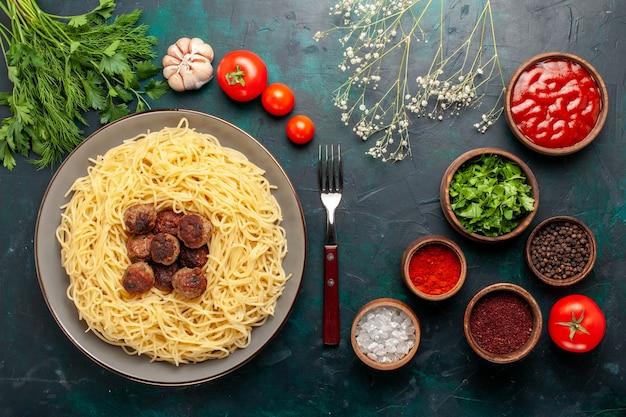 紺色の机の上にミートボール調味料と緑のトップビュー調理イタリアンパスタ 無料写真