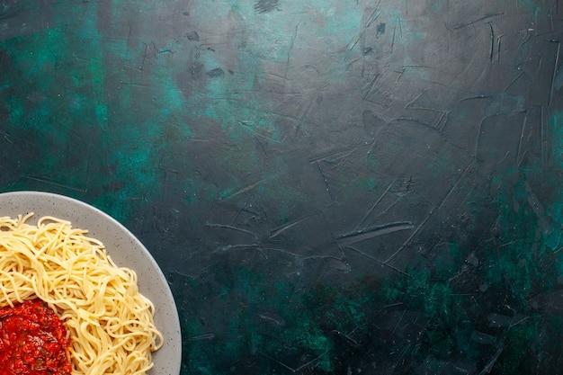 Vista dall'alto cucinato pasta italiana con carne macinata e salsa di pomodoro sulla superficie blu scuro Foto Gratuite