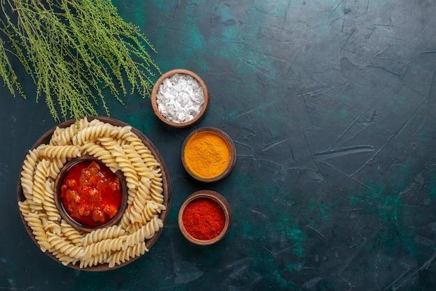 Vista dall'alto cucinato pasta italiana con salsa e condimenti diversi sulla scrivania scura Foto Gratuite