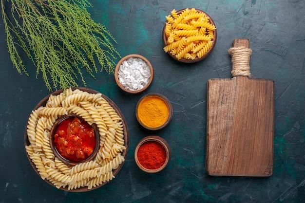 Vista dall'alto cotta pasta italiana con salsa e diversi condimenti sulla superficie scura Foto Gratuite