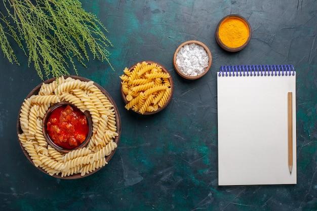 Vista dall'alto cucinato pasta italiana con salsa e condimenti sulla scrivania scura Foto Gratuite