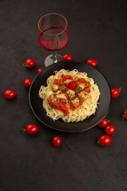 Вид сверху приготовленная паста с куриными крылышками и томатным соусом внутри черной тарелки на темном полу Бесплатные Фотографии