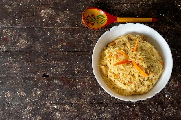 Una vista dall'alto ha cucinato il riso salato e pepato gustoso all'interno del piatto rotondo su fondo rustico Foto Gratuite