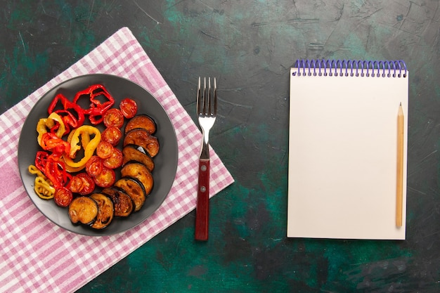 Top view cooked sliced vegetables bell-peppers and eggplants with notepad on dark-green surface Free Photo