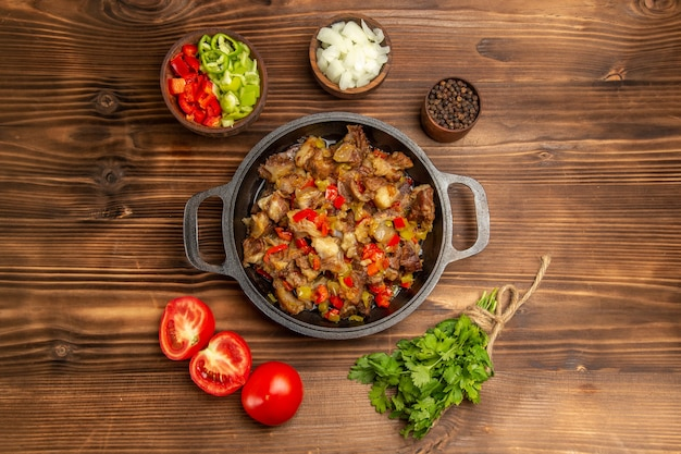 나무 갈색 책상에 고기와 신선한 얇게 썬 피망으로 요리 한 야채 식사 무료 사진