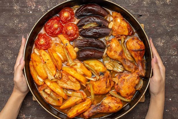 トップビュージャガイモトマトやナスなどの野菜を鍋に茶色で調理 無料写真