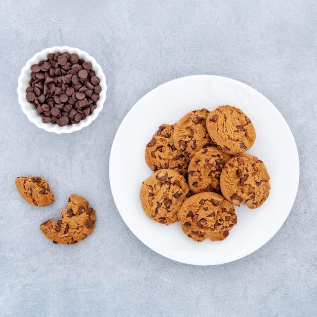Biscotti di vista dall'alto e gocce di cioccolato nella ciotola Foto Gratuite