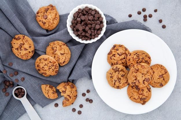 Biscotti di vista dall'alto e gocce di cioccolato sul panno Foto Gratuite