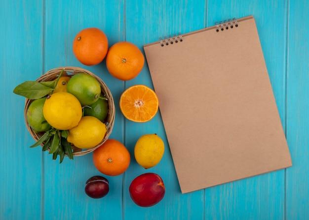 Top view copy space beige blocco note con sapels limoni e limette in un cesto su uno sfondo turchese Foto Gratuite