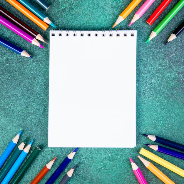 Top view copy space colorful pencils with notepad on a green background Free Photo