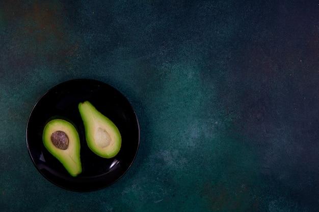 진한 녹색 배경에 검은 접시에 반 아보카도에서 잘라 상위 뷰 복사 공간 무료 사진