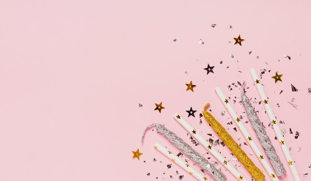 Top view copy space frame with candles and glitter on pink background Free Photo