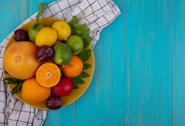 Вид сверху копия космического грейпфрута с апельсинами, сливами, лимонами и лаймами на желтой тарелке на клетчатом полотенце на бирюзовом фоне Бесплатные Фотографии