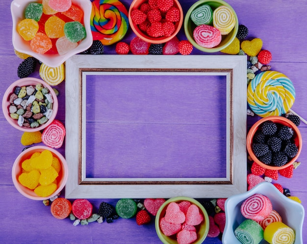 Top view copy space gray frame with multi-colored marmalade chocolate stones and colored icicles in saucers for jam on a purple background Free Photo